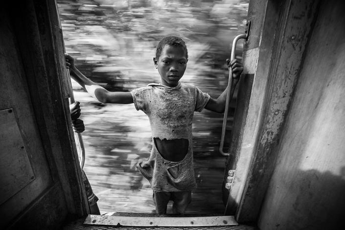 Un jeune garçon s'accroche au train de la FCE. Madagascar