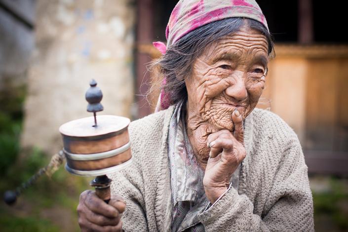 Vieille femme tamang avec un moulin à prière - Népal