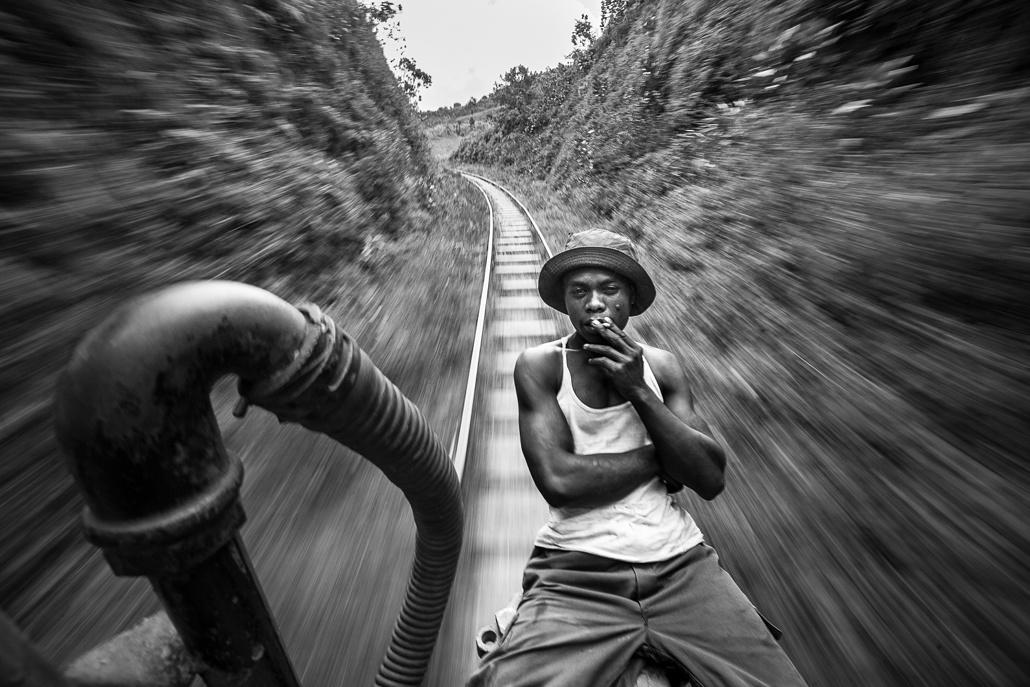 Un mécanicien du train de la FCE fume une cigarette à l'avant de la locomotive. Madagascar