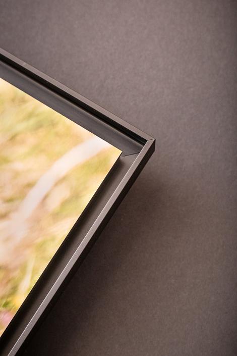 Détail de finition pour les tirages d'art montés dans une caisse américaine en aluminum anodisé noir.